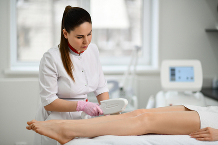 Young doctor-cosmetician performs a cosmetic procedure on the patients legs hips with electronic medical equipment laser in beauty shop
