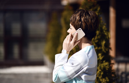 Successful woman talks by cell phone on background of modern business centre courtyard