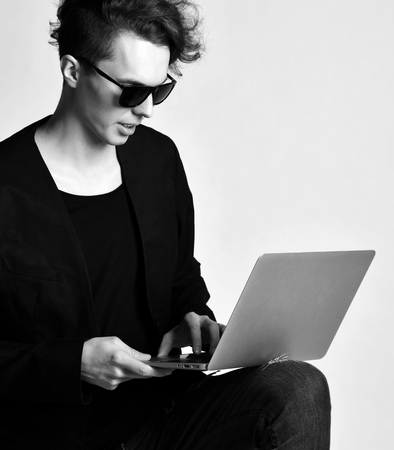 Young modern man in jeans black jacket suit and sunglasses work on laptop computer that holds on his knee. Closeup. Black and White.