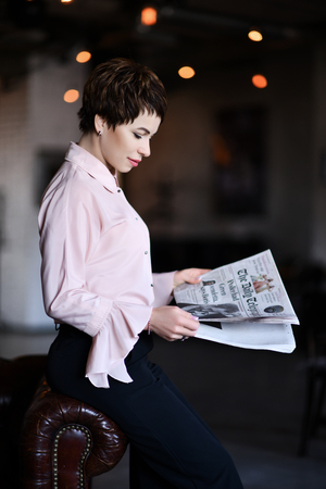 Business woman in modern fashion official suit reads a business news papers during her break on background of modern office 写真素材