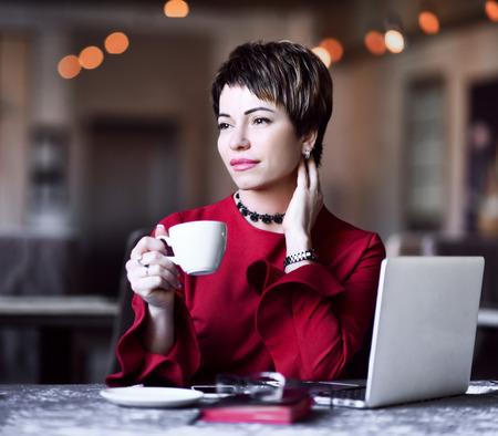 Erfolgreiche Geschäftsfrau mit Laptop vor sich macht eine Pause mit einer Tasse Tee oder Kaffee Standard-Bild
