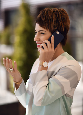 Successful woman in fashion office suit talks by phone and laughs on background of modern office or business centre
