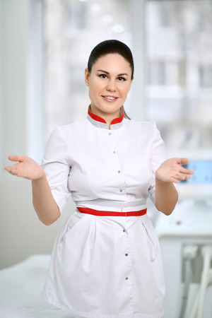 Young brunette doctor cosmetician in medical uniform white medical gown on background of beauty parlor gesticulates actively