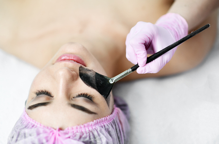 Cosmetician in cabinet preparing patient for a cosmetic procedure gently applies a clay composition with a brush in beauty parlor