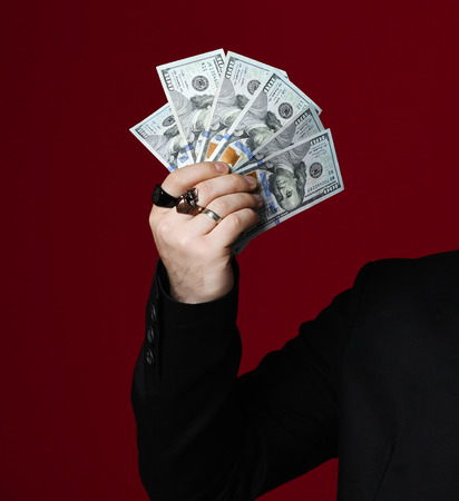 Business man hand holding American dollars banknotes on red Фото со стока