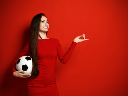 Pretty brunette woman in tight red dress with soccer ball in her hand looks up dreamly and calculates winnings on red background with free text space
