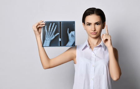 Brunette woman with a straight face doctor or clinic patient demonstrates hands X-ray examination and lifted her finger up reinforcing the importance