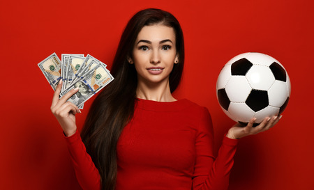 Smiling pretty brunette in tight red dress holds soccer ball and bundles of dollars on red background