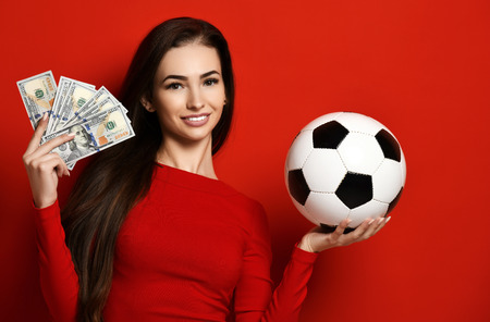 Young woman in red uniform hold soccer ball and dollar money for sports betting celebrating happy up with free text copy space on red background