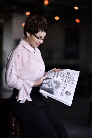 Business woman in glasses and modern fashion official suit reads a business news papers during her break on background of modern office 写真素材