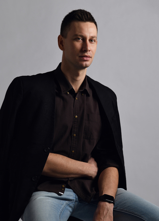 Self-confident modern businessman in shirt with roll up sleeves, jacket hanging on shoulders and blue jeans sits in relaxed pose and looks at us