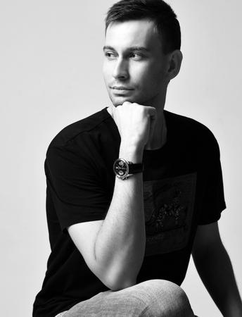 Junger gutaussehender Mann in Freizeitkleidung mit seinem Kinn auf der Hand sitzt mit einem leichten Lächeln auf einer Stufenleiter-Aussicht. Schwarz und weiß Standard-Bild