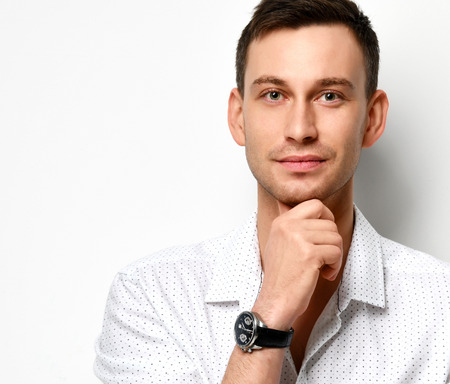 Young man in white casual shirt with a slight smile holds his chin with his hand on white background