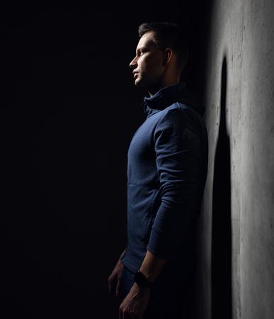 Tiro lateral de joven atlético en chándal de ropa deportiva azul se encuentra cerca de muro de hormigón con sombra. Fondo negro con espacio de texto libre Foto de archivo