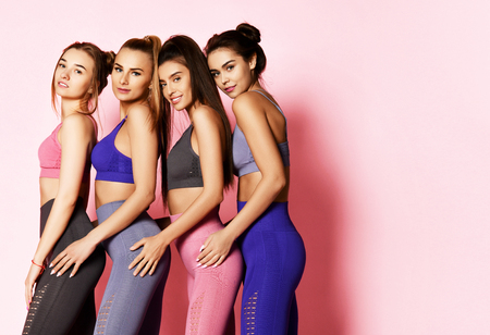 Athletic women in blue, grey, brown standing behind each other. Fitness and workout girls posing on pink background with text copy space behind them