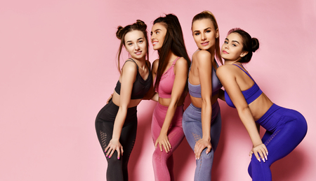 Young and athletic sport girls posing on pink background with free text space. Fitness and yoga instructors in blue, grey, brown training suits