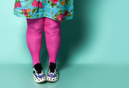 Overweight fat woman legs in modern pink leggings and sneakers close up on blue mint