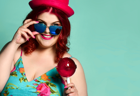 Happy smiling overweight fat chubby woman in hat and sunglasses with extra big lollipop on popular blue mint background