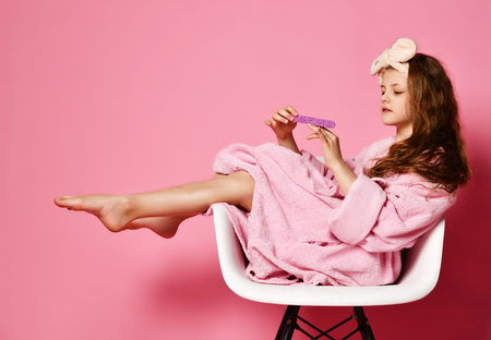 Young lady kid in bathrobe sits in fashion designer armchair takes rest relax and make manicure on pink. Beauty concept on pink background
