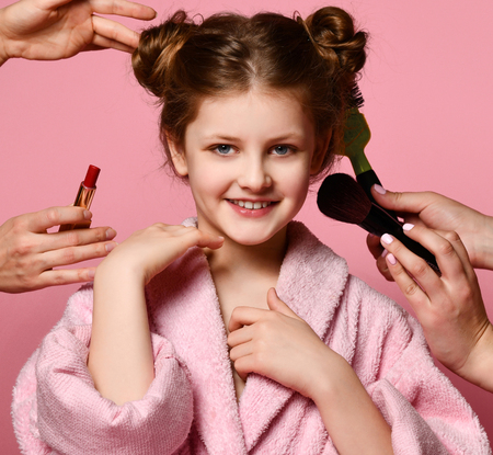 Happy smiling young lady teen girl in spa salon during makeup and  hair style. Beauty concept on pink background Stock Photo
