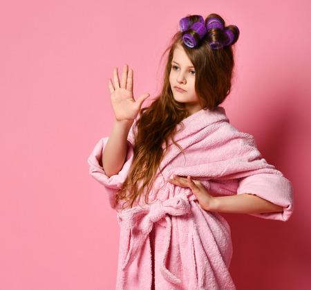 De veeleisende tienerdame van het meisje met krulspelden in haar in badjas toont Wacht een tweede tekengebaar. Schoonheid mode levensstijl concept op roze achtergrond