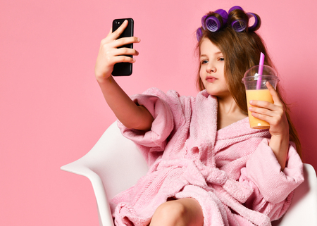 Young cheeky lady teen girl in bathrobe and with hair in curlers in beauty shop drinks smoothie fresh juice and have fun taking cool fashion look selfie. Beauty concept on pink background with text copy space