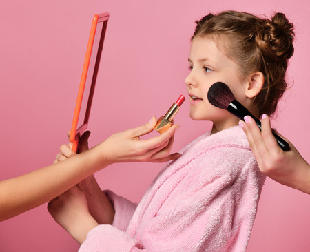 Pretty young lady teen girl with buns in spa salon during makeup and hair style evaluates her visage in the hand mirror on pink. Beauty concept on pink background Stock Photo