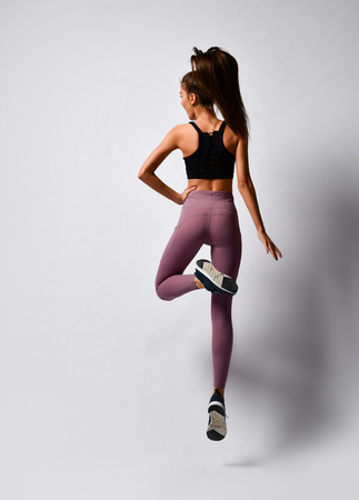 Slim brunette woman running jumping doing workout exercise in sport wear from back on gray