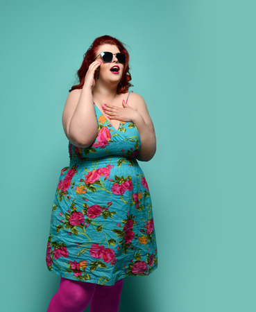 Surprised plus-size lady overweight woman in hat, sunglasses and colorful clothes looks at something incredible or amazing offer on mint