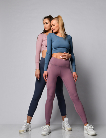 Two sporty blonde and brunette girls in athletic body cloth sport wear cloth stand together after workout on gray background Stock Photo