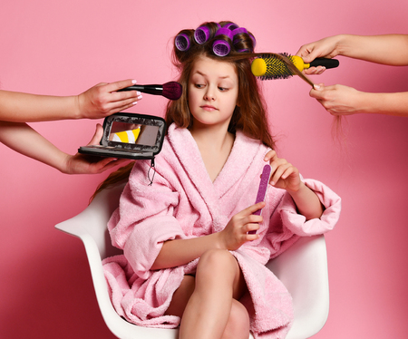 Exacting young lady teen girl in spa salon evaluates makeup offered to her while making hair style and manicure. Stock Photo