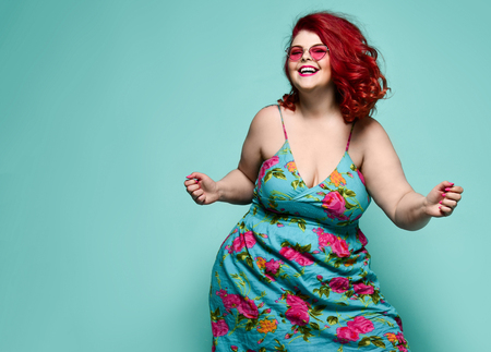 Lucky plus-size lady overweight woman in fashion sunglasses and colorful sundress happy dancing, celebrating on mint background with free text space