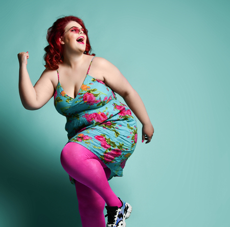 Loud laughing plus-size lady overweight woman in fashion sunglasses and colorful sundress running from something on mint background with free text space Imagens