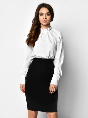 Young beautiful woman posing in light-dark office suit. Light blouse and dark pencil skirt on a white background