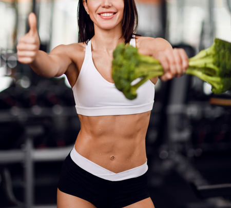 Closeup. Diet and weight loss concept. Athletic woman fitness instructor with perfect abs recommends proper nutrition holding big broccoli and showing thumb up on background of gym equipment