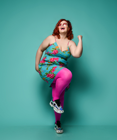 Happy laughing plus-size redhead woman overweight in fashion sunglasses and colorful clothes dancing, showing Yeah sign with her arm on mint background