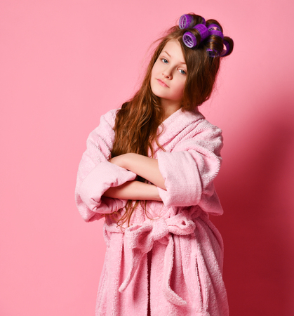 Young teen girl in bathrobe and with hair in big curlers rollers stands with displeased face and crossed arms like an angry wife on pink background Stock Photo