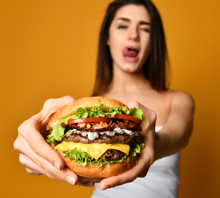 Woman eat burger sandwich with hungry mouth on yellow background. Closeup composition of Fast food concept Reklamní fotografie