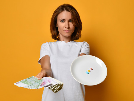 Woman nutritionist hold a white plate with different color tablet pills diet supplements prescription weight loss drugs on yellow background