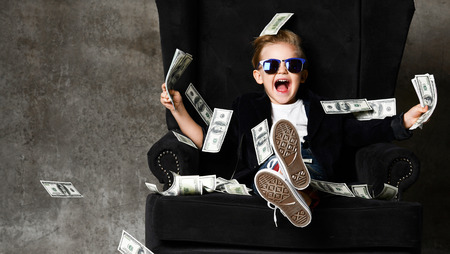Happy young boy crazy screaming excited hold stack of dollars money. Guy celebrates success lots of money dollar bills banknotes sitting in chair