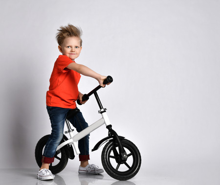 Young boy kid in orange t-shirt biker ride bicycle happy screaming on white background Reklamní fotografie