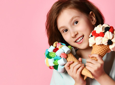 Baby girl kid eating hold two big ice cream in waffles cone with tasty raspberry marshmallow marmalade happy smiling on pink background