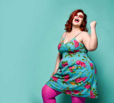 Lucky laughting loud plus-size lady overweight woman in sunglasses and colorful clothes shows Yes sign gesture with her arm on mint background with free text copy space Reklamní fotografie