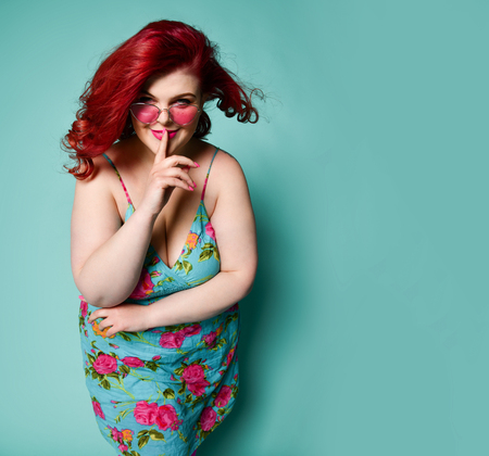Plus-size overweight redhead lady plus-size woman in sunglasses shows Shhh gesture sign with her finger on lips and smiles enigmatically, asks to keep a secrete on mint background Imagens