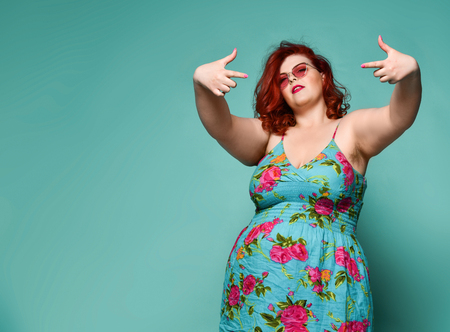 Self-confident and danger plus-size overweight redhead lady in sunglasses and sundress shows a gesture sign finger - gun like a cool rapper on mint background with free text copy space Reklamní fotografie