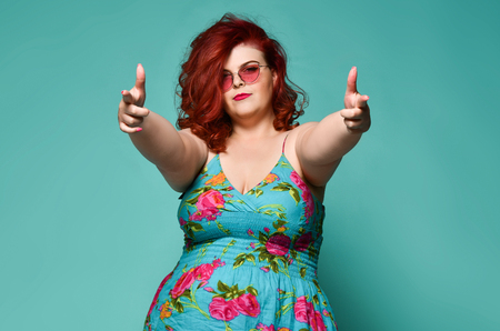 Self-confident plus-size overweight redhead lady in sunglasses and sundress shows a gesture sign finger - gun, aimed at us on mint background