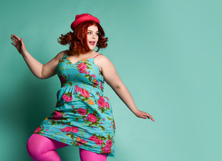 Loud laughing plus-size lady overweight woman in funny hat, colorful sundress and tights jumping funny or running away from something on mint background with text copy space