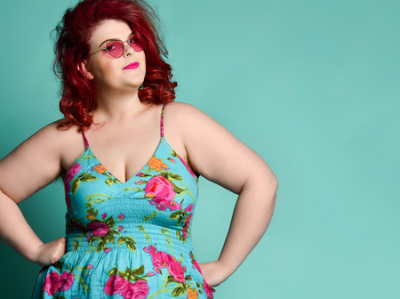 Pretty plus-size fat woman in fashion sunglasses with enigmatic mysterious face looks at us like she suspects us of prank or trick on mint background