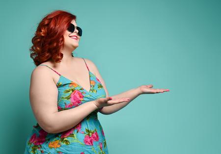 Bella donna grassa plus-size sorridente in occhiali da sole alla moda e prendisole colorato si erge di profilo con la testa leggermente piegata e dimostra qualcosa sui suoi palmi aperti su sfondo menta
