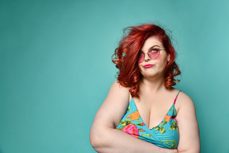 Deaf for arguments plus-size overweight lady in sunglasses and sundress with her arms crossed and rolled eyes does not believe in something on mint background with free text copy space Reklamní fotografie